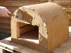 Lehmverarbeitung: Pizzaofen mit Lehm verputzen